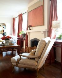 A linen-upholstered armchair with nailhead trim is quietly ...