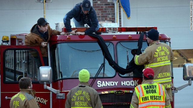 Firefighters Attach Black Bunting To A Fire Truck As A