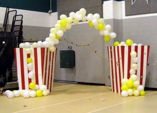 Yellow/white balloon arch + red and white striped pillars