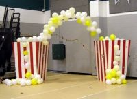 Yellow/white balloon arch + red and white striped pillars ...