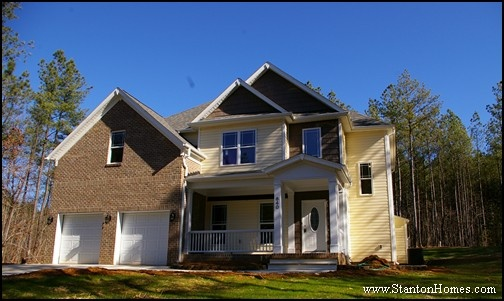 Two story new home with cozy covered front porch brick accents prairie grid windows dual