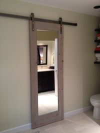 Sliding bathroom door. Gray toned antique wood.
