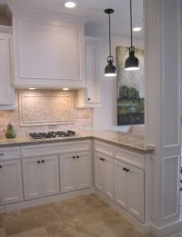 Kitchen with off white cabinets, stone backsplash and ...