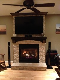 Stone on fireplace with tv mounted over mantle. I like the