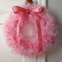 The wreath is tied with layered coral pink, light pink and ...