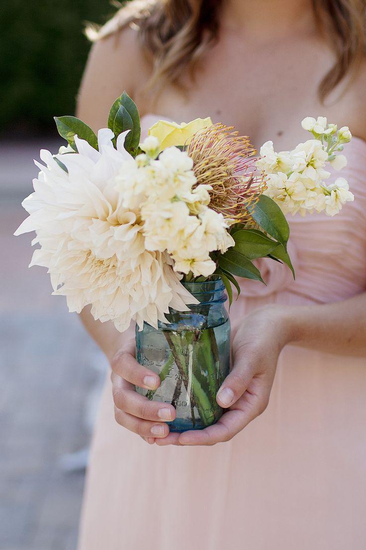 blue mason jar centerpiece blush dahlia yellow pincushion protea yellow stock craspedia