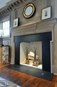 Gray washed millwork, black stone fireplace surround ...