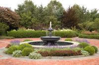 An aluminum & lead fountain in circular driveway in front ...