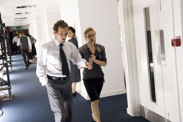 Men And Women Wearing Business Suits Walk Hallway