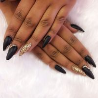 Stiletto nails in matte black with gold glitter and ...