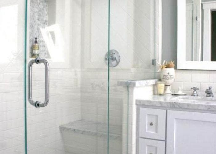 glass enclosed shower with white tile walls and gray mosaic floor is also
