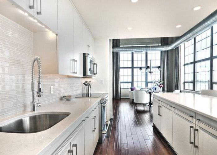 Glass tile backsplash high ceilings and handscraped hardwood floors really look great against the also