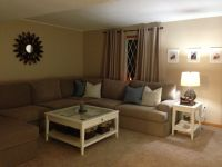 with white walls tan couch and brown carpet. Blue curtains