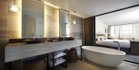 A hospitality bathroom design with a sliding door that ...