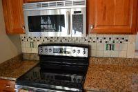 Tiled kitchen backsplash below and behind the microwave ...