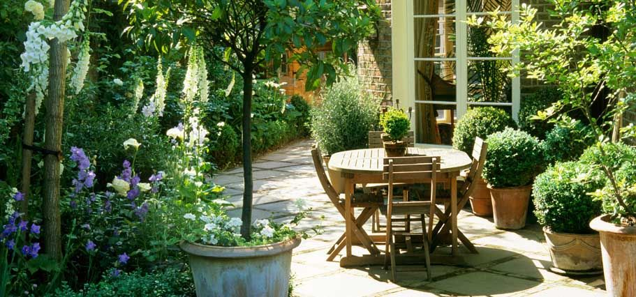 A Pretty Patio Area Love How The Pots Of Green Bushes Softens The