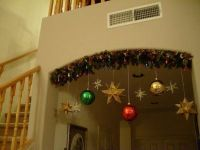 Lighted garland over entryway with hanging ornaments ...