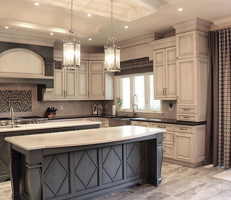 Dark grey island with white countertop and antique white