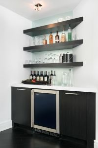 This modern wet bar features floating corner shelves and a ...
