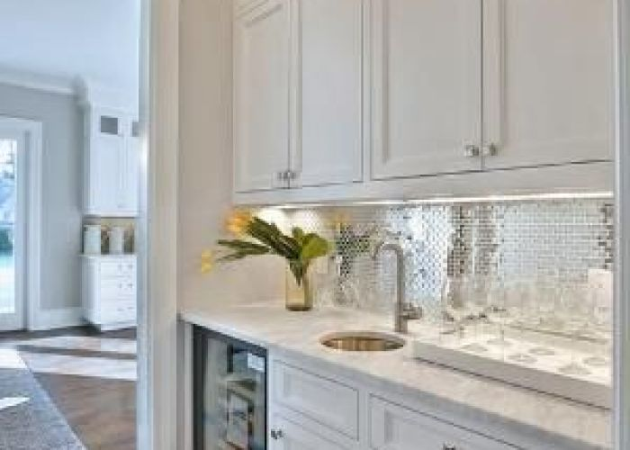 White and silver butler   pantry features shaker cabinets paired with carrera marble countertops fitted glass tile also
