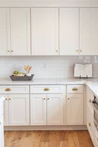 White shaker cabinetry with brass cups and knobs
