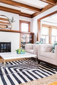 White painted brick, natural wood trim, neutral chairs ...
