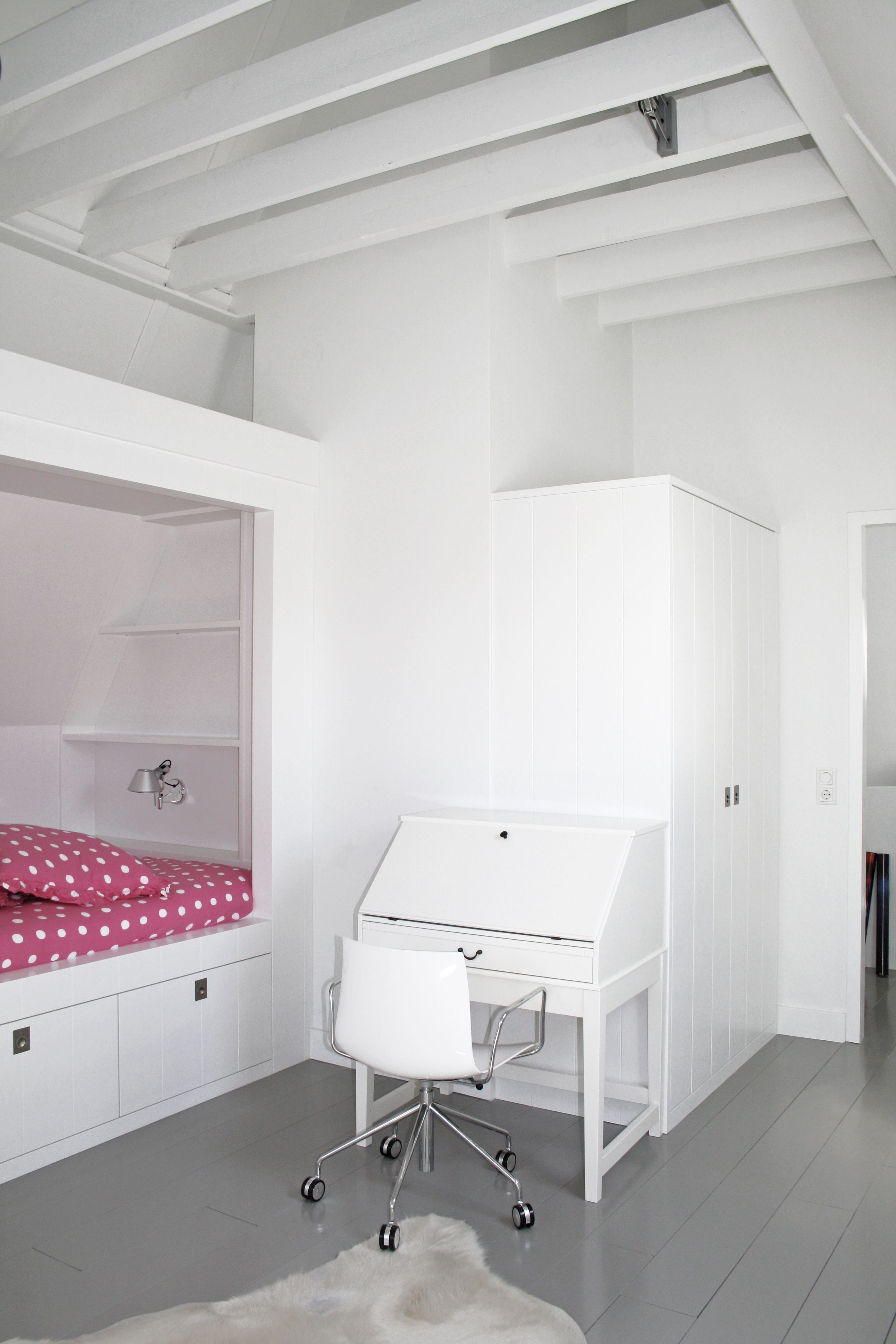 Slaapkamer bed onder schuin dak grijze houten vloer