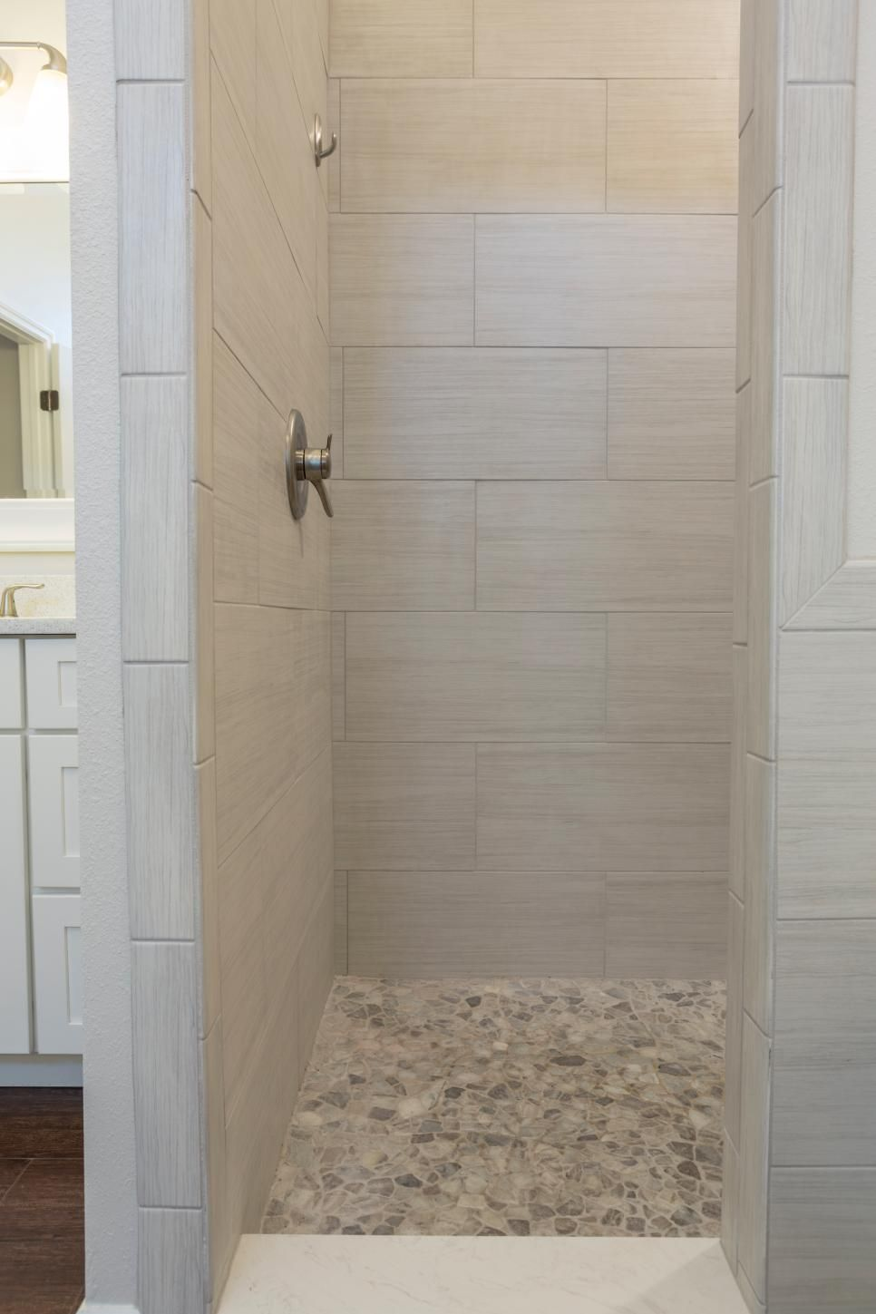 Sleek yet soft gray tiles carve out a gorgeous walkin shower in this transitional bathroom