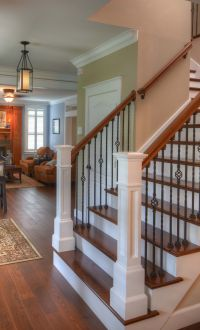 Hardwood flooring up the stairs = classic look. Rod Iron