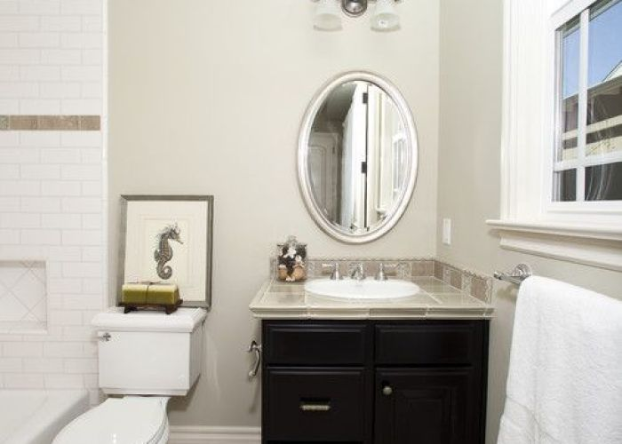 Tiny black bathroom vanities with tops and white planted sink under silver framed oval wall mirror also