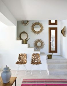 An array of sunburst mirrors and  pair wrapped rattan chairs combine for eye catching composition against this mallorcan home   crisp white walls also pin by          on     pinterest interiors rh