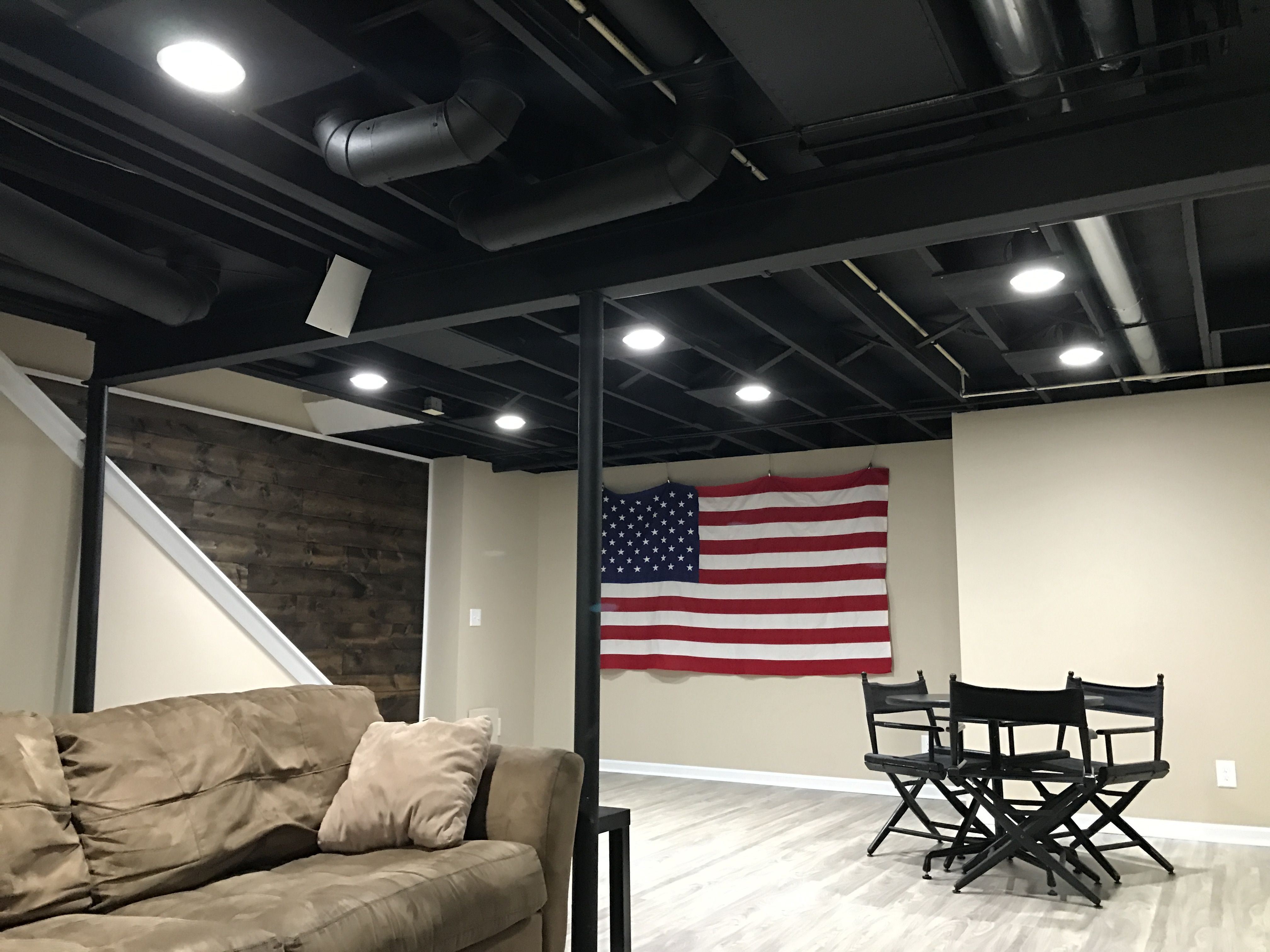 Exposed basement ceiling painted black.