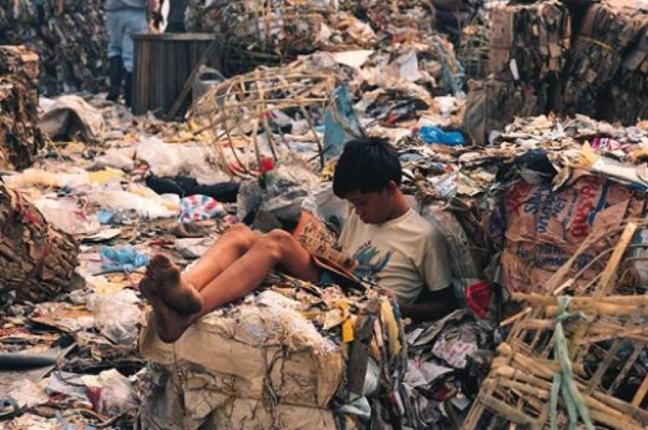 Teenage Asian man reading on a pile of rubbish in a dump site