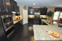 Dark kitchen cabinets and light granite countertop ...