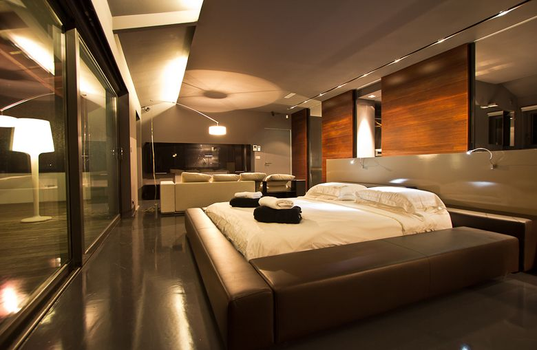 Ultra modern bedroom with leather bed and small living ...