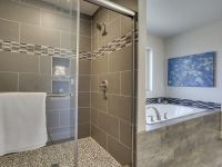 Tile shower with inset shelves & pebble floor. Garden tub ...