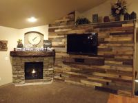 Pallet wood wall and stone fireplace surround with a ...