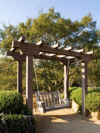 A lovely wooden arbor with attached swing is bordered by ...