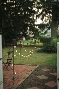 Tiki torches and solar lights border patio area. Simple ...
