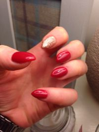 Red stiletto gel nails with gold glitter index finger ...
