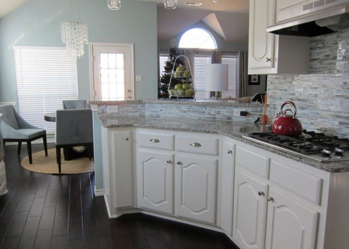 White cabinets with tile floor wood flooring and glass backsplash along also