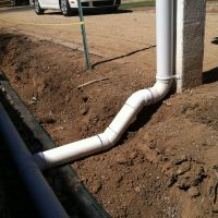 Solid pipe connects the downspout to the perforated pipe