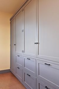 A wall of built-in cabinets provides plenty of room to ...
