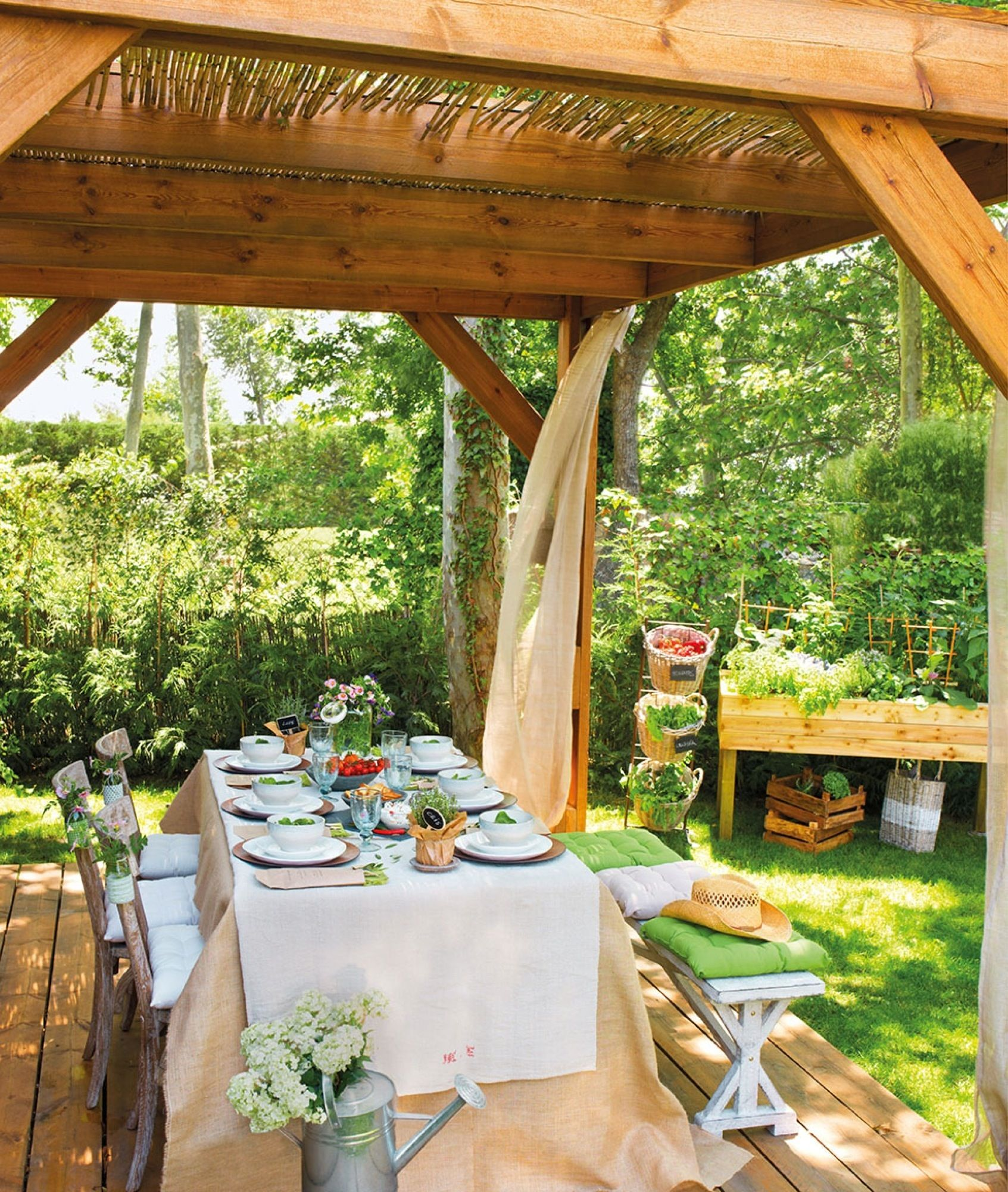 Comedor bajo prgola de madera y caas con cortinas y