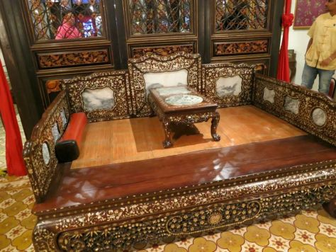 A Peranakan day-bed. The red and black block on the left is a traditional Peranakan pillow. The black ends were usually decorated with plaques made of gold or silver, which were secured onto the sides with nails.