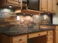 This natural slate tile backsplash is shown with Uba Tuba ...