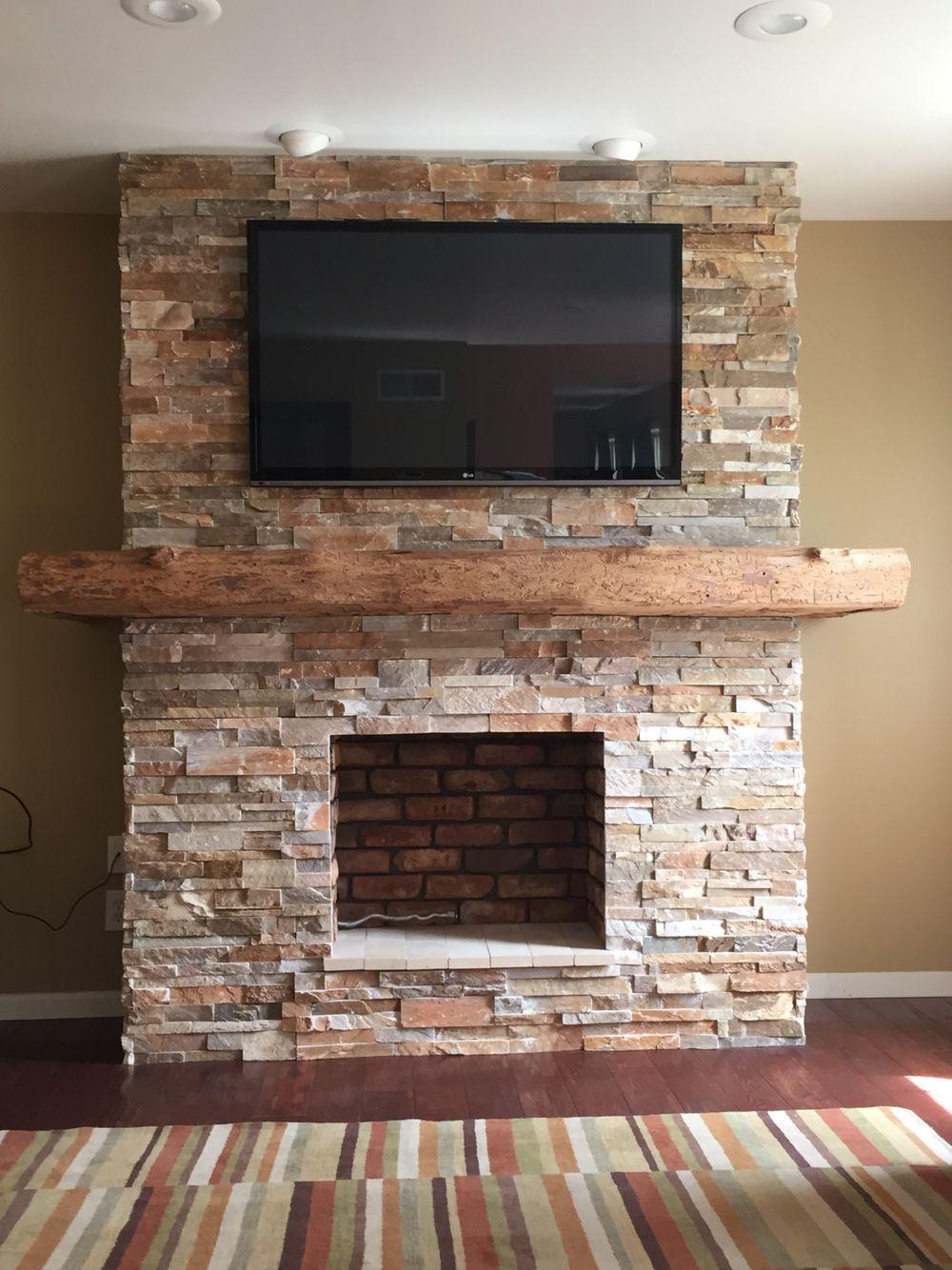 Stone fireplace with wrap around barn beam mantel