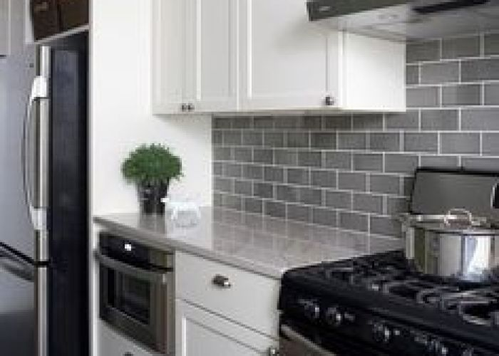 Light gray subway tile backsplash with dark grey floors and white cabinets love this also kitchen tiles transitional