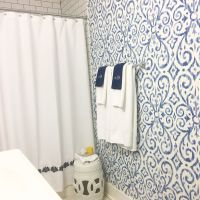 blue and white bathroom with Ikat print wallpaper by