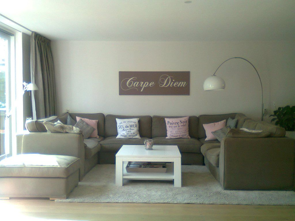 woonkamer met hoekbank in taupe met roze en witte styling